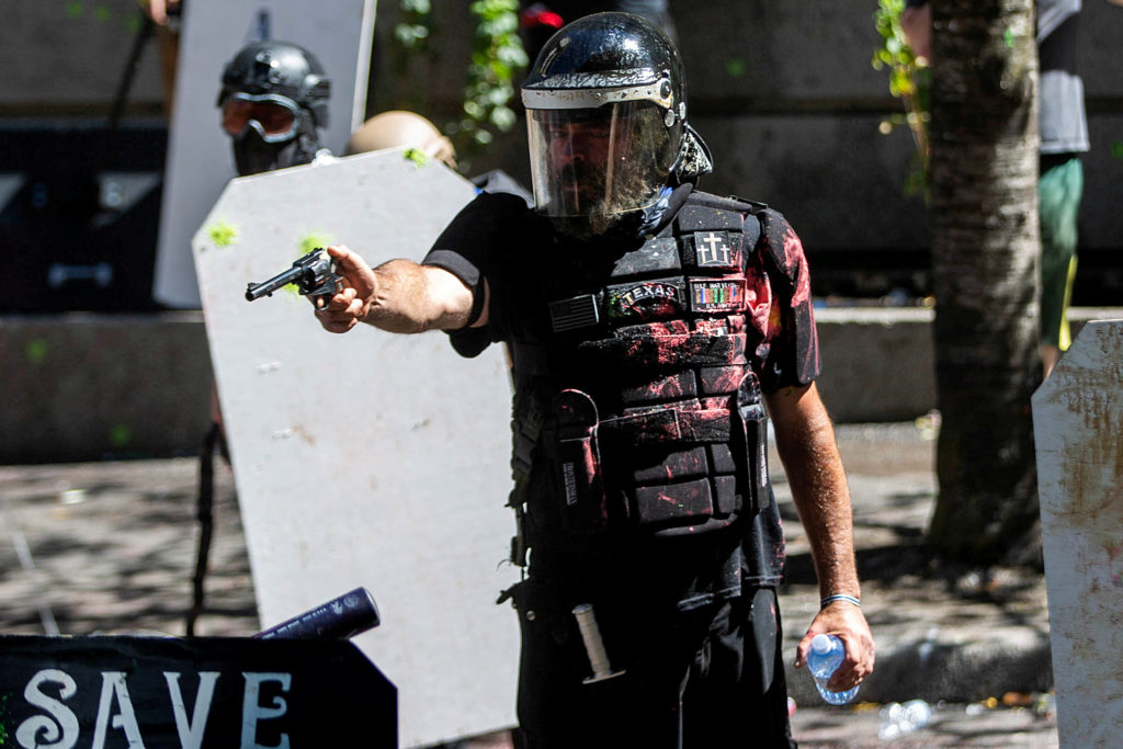 Alan Swinney points a gun during clashes between groups like Proud Boys and Patriot Prayer, and protesters against police brutality and racial injustice in Portland, Oregon, U.S., August 22, 2020.